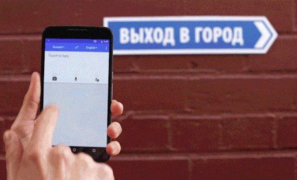 Smartphone en manos contra muro con cartel en ruso