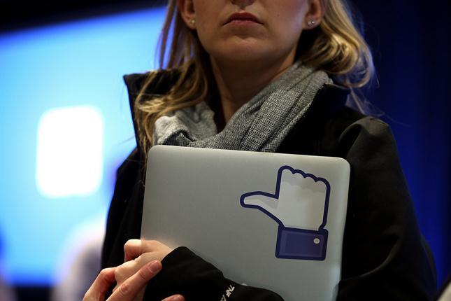 Mujer con laptop en la mano con calcomanía de Me Gusta de Facebook