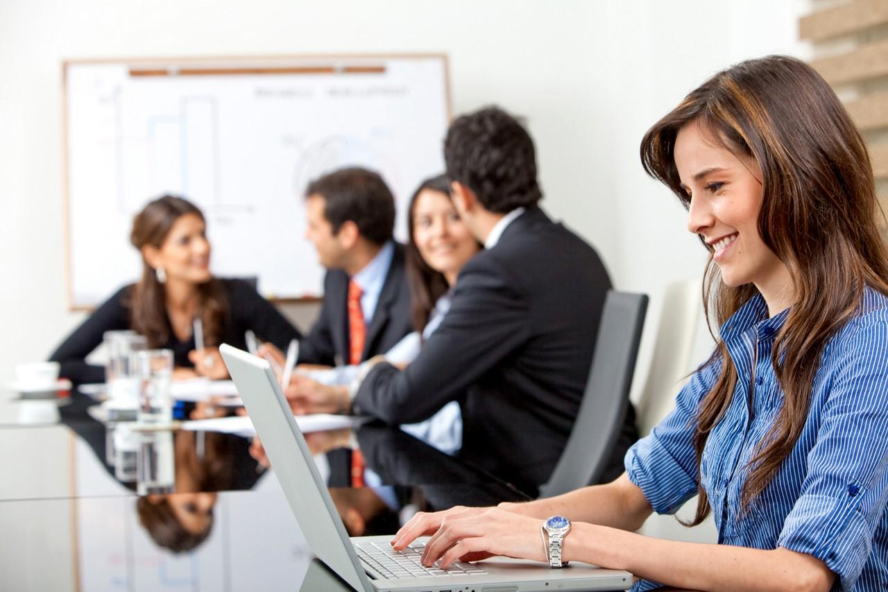 Mujer trabajando con laptop en reunión.
